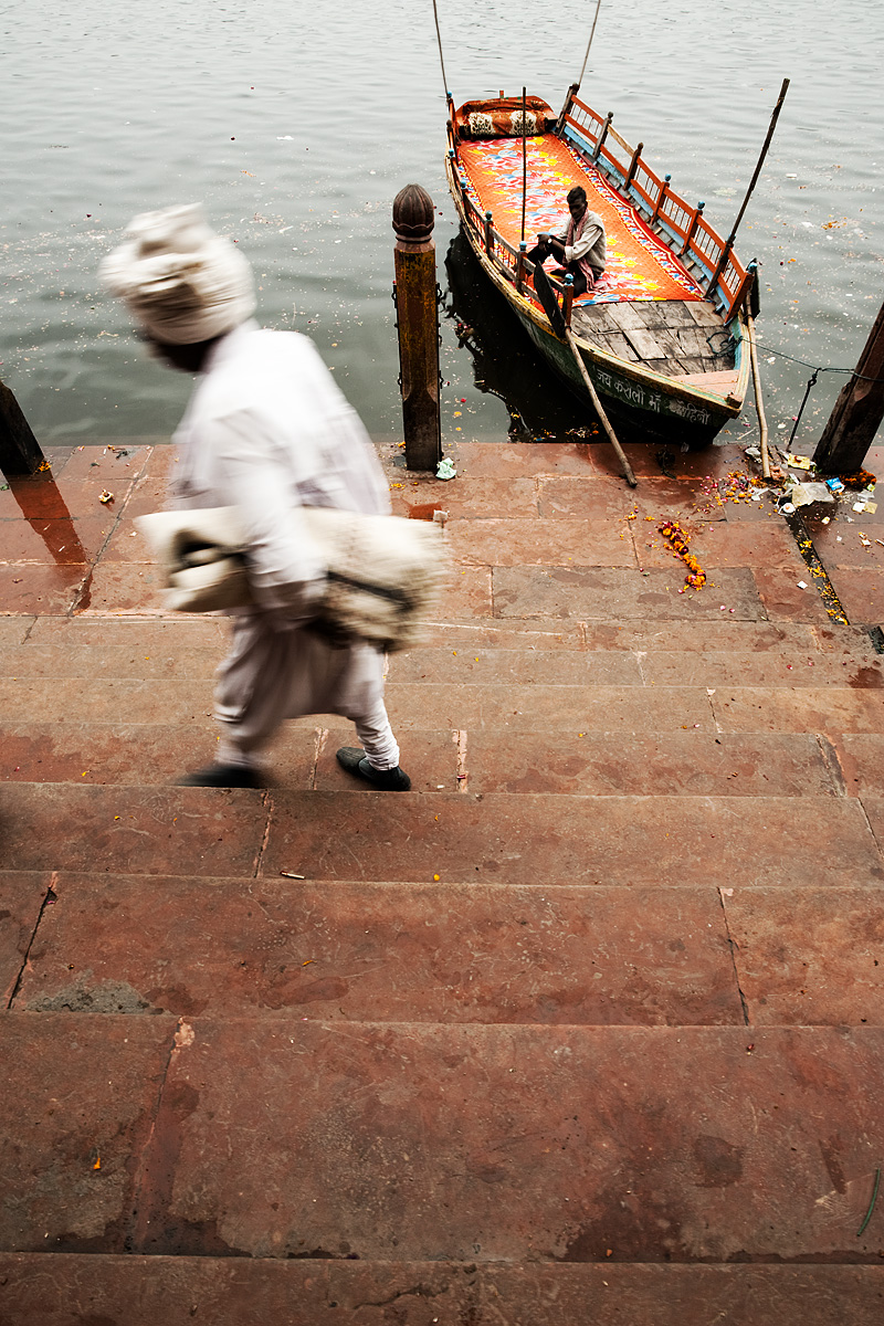 A boat man on the holy Jamuna river watches a pilgrim blur by. - Mathura, Uttar Pradesh, India - Daily Travel Photos