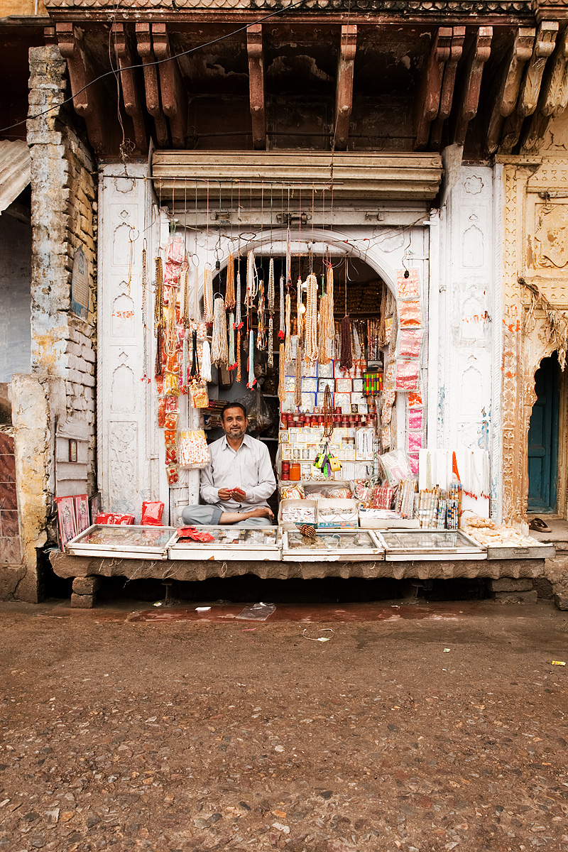 A store owner sits cross-legged in his low jewelry shop. - Mathura, Uttar Pradesh, India - Daily Travel Photos