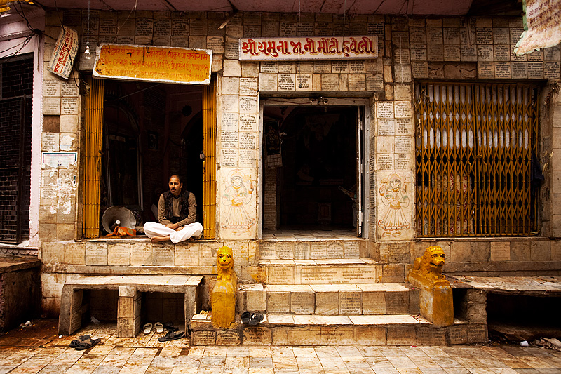 A caretaker sits cross-legged on the window of a temple. - Mathura, Uttar Pradesh, India - Daily Travel Photos