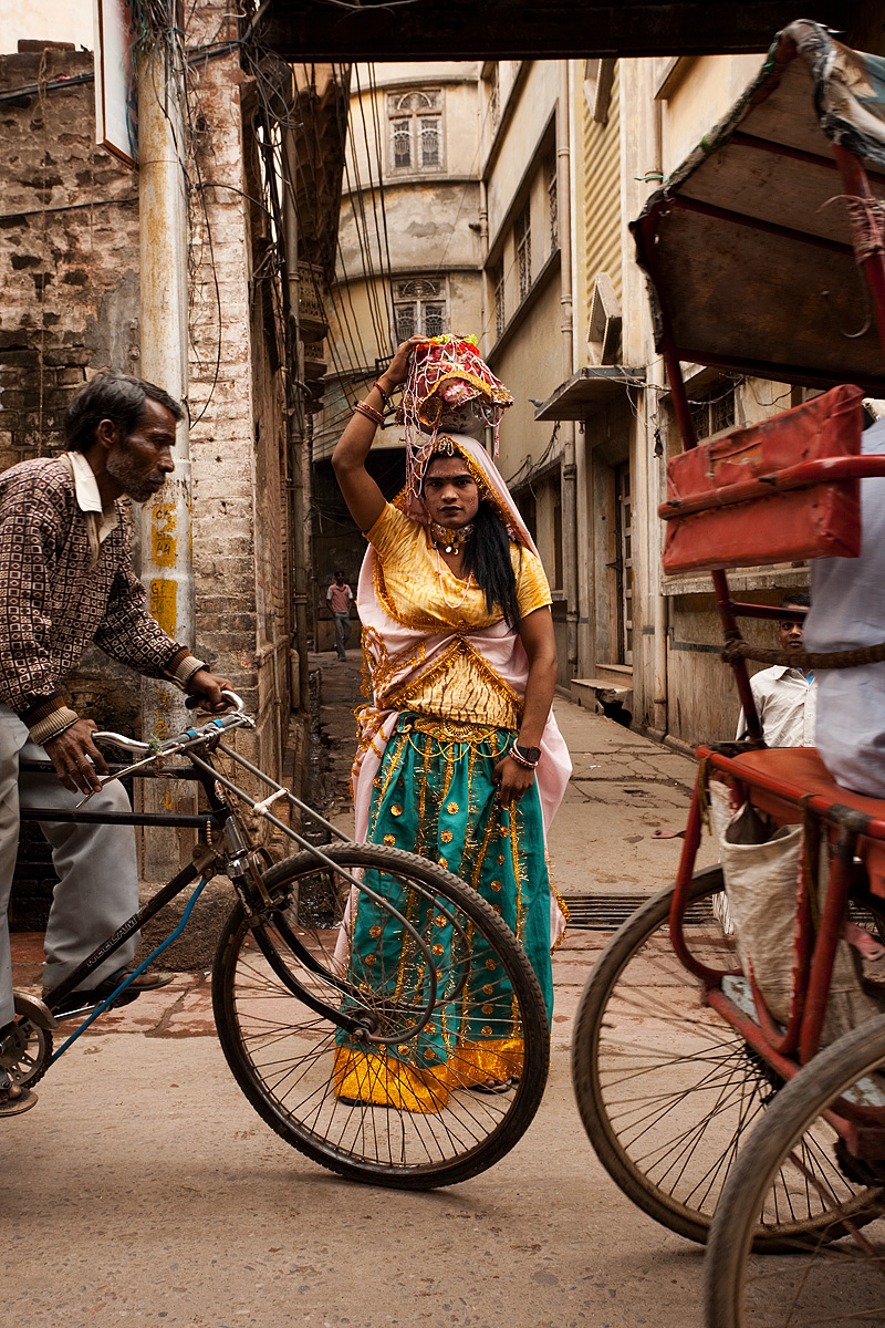 A man dressed as a woman stands amid light traffic. - Mathura, Uttar Pradesh, India - Daily Travel Photos