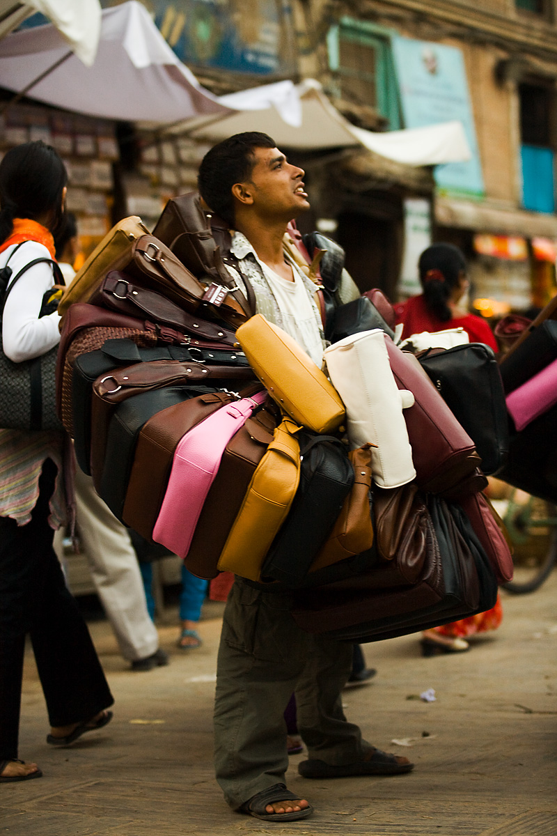 A salesman is encircled by a ring of women's handbags. - Kathmandu, Nepal - Daily Travel Photos