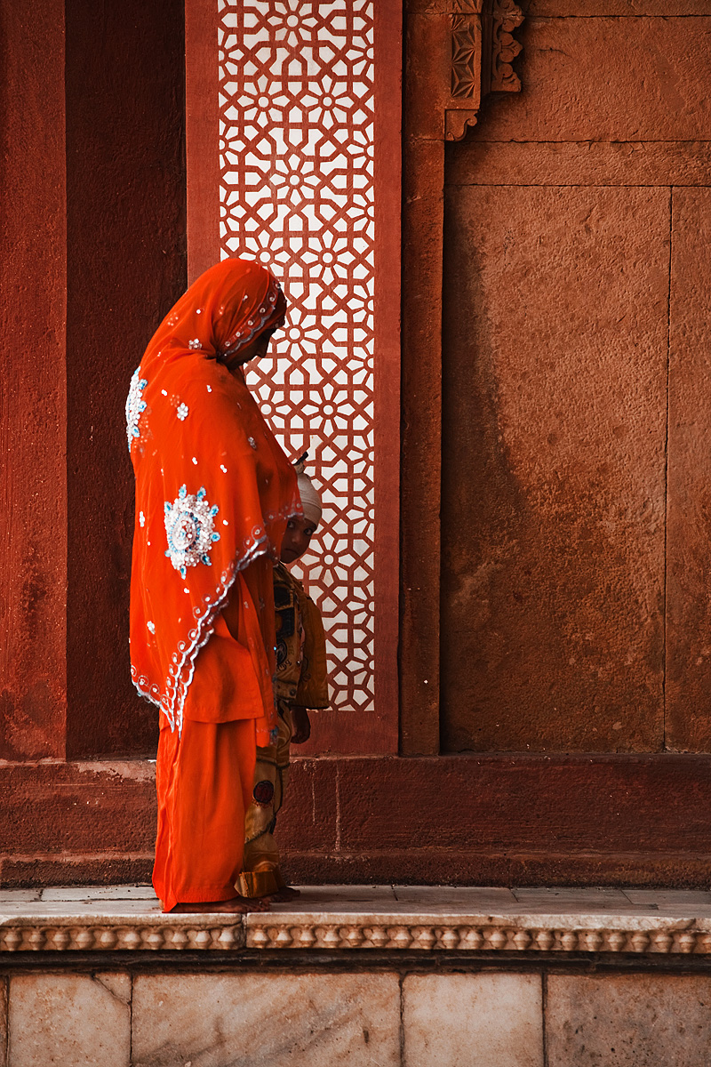 A child spies suspiciously while his mother prays. - Fatehpur Sikri, Uttar Pradesh, India - Daily Travel Photos
