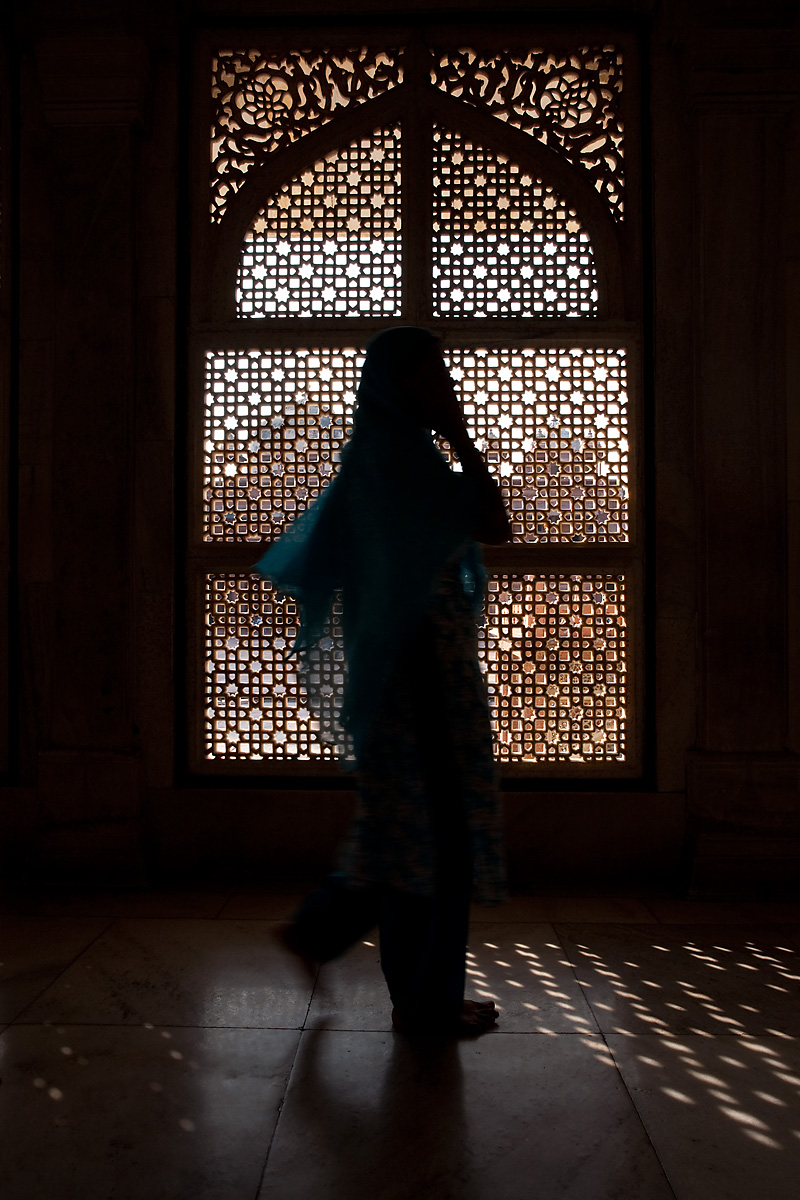 A Muslim woman walks in front of an intricately carved lattice window. - Fatehpur Sikri, Uttar Pradesh, India - Daily Travel Photos