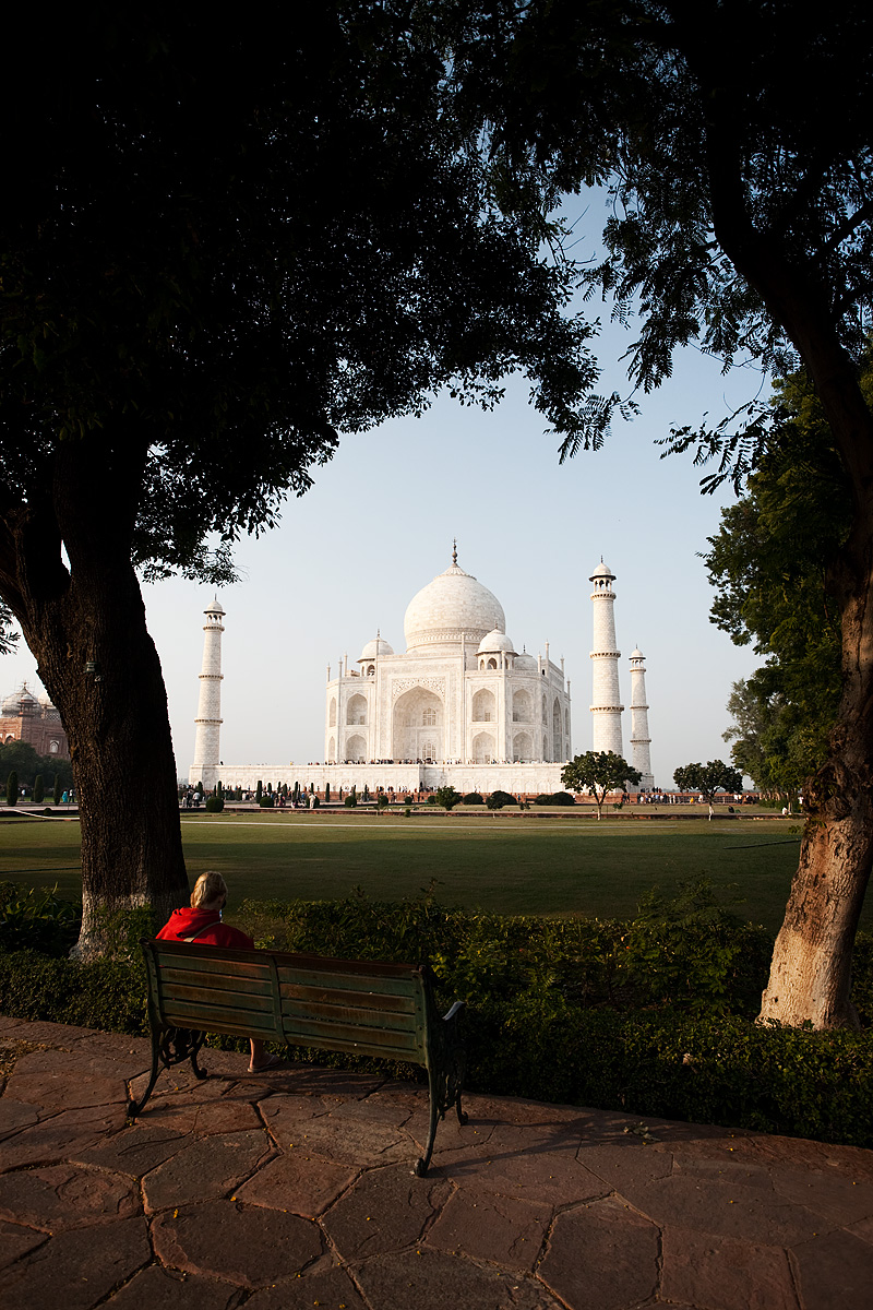 A young foreigner reads on a park bench at the Taj Mahal. - Agra, Uttar Pradesh, India - Daily Travel Photos