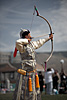 Markswoman Photo: The archery portion of the Naadam Festival held in July each year.  A female archer in elegant Mongolian dress aims to topple a small wall of marked blocks from over half a football field away.  The skill demonstrated by the archers in the competition is absolutely amazing as they more often than not hit the center portion of the marked blocks.  What's even more amazing, to me at least, is that they arc the arrows at the target as you can see from the position of this archer's bow, yet still manage to hit the target consistently.