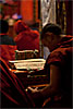 Cushion & Text Photo: A young Tibetan monk breaks from his chants to organize his prayer sheets.