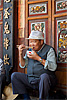 Foodie Photo: A Chinese man delicately places a morsel of food into his mouth.  Is it just me or does anyone else like the character on the man's face?  He's got the benign appearance of a friendly uncle that makes me want to be friends with him.
