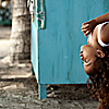 Curly Photo: A young Balinese girl surveys the scene on her father's lap at Kuta beach in Bali.