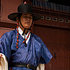 Gatekeepers Photo: A guard carrying the royal flag stands aside the main entrance to Gyeongbokgung Palace.
