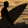 Frothy Walk Photo: A pair of surfers head home after an evening of catching waves at touristy Kuta beach in Bali.