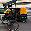 Roti-Powered Photo: A cycle rickshaw driver offers a quick glance in busy downtown traffic.