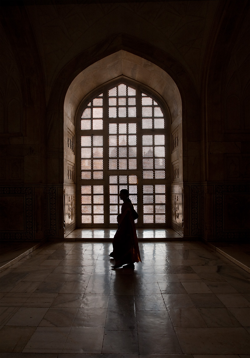 A mother and child walk in front of a large lattice screen window inside the Taj Mahal tomb. - Agra, Uttar Pradesh, India - Daily Travel Photos