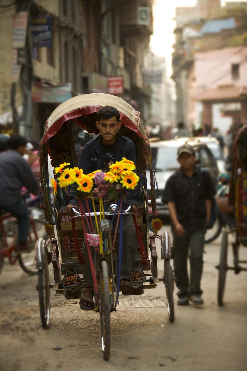 A flower-decorated cycle-rickshaw rolls down a poorly paved road in Kathmandu. - Kathmandu, Nepal - Daily Travel Photos