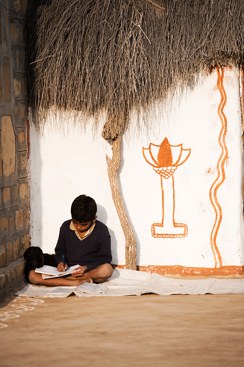 A boy and his goat put the finishing touches on his homework before the start of school. - Khuri. Rajasthan, India - Daily Travel Photos