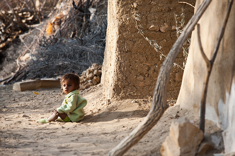 A toddler sits alone in the sand outside his mud wall home. - Khuri. Rajasthan, India - Daily Travel Photos