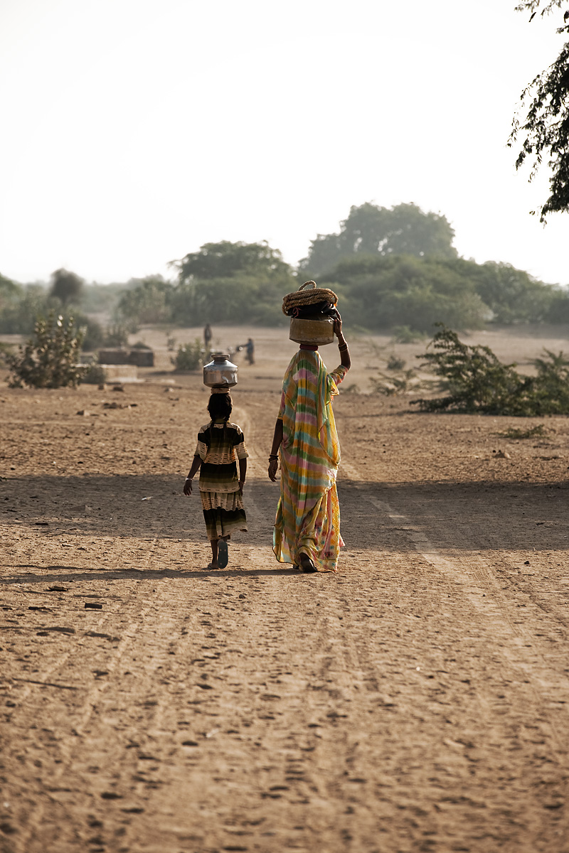 Mother and daughter balance pots on their heads to transport water from the village water tank. - Khuri. Rajasthan, India - Daily Travel Photos