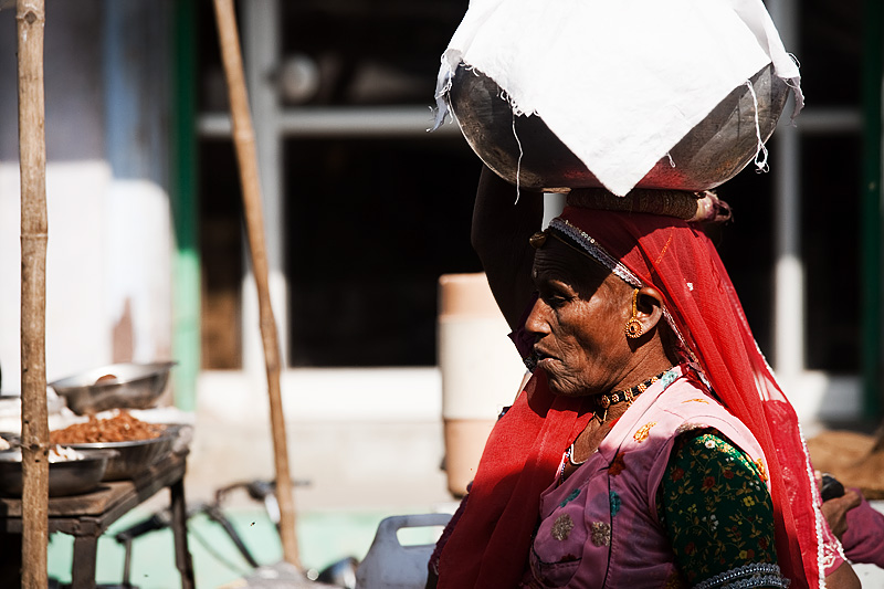 A Rajasthani woman uses her wicker halo to pad her head against a metal pot. - Jodhpur, Rajasthan, India - Daily Travel Photos