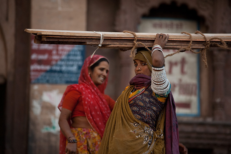 A working Rajasthani woman hauls lumber atop her head. - Jodhpur, Rajasthan, India - Daily Travel Photos