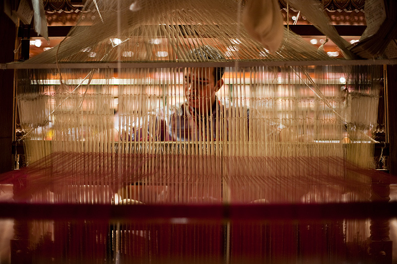 The weaver is seen through the white operating strings of the loom. - Tirunelveli, Tamil Nadu, India - Daily Travel Photos