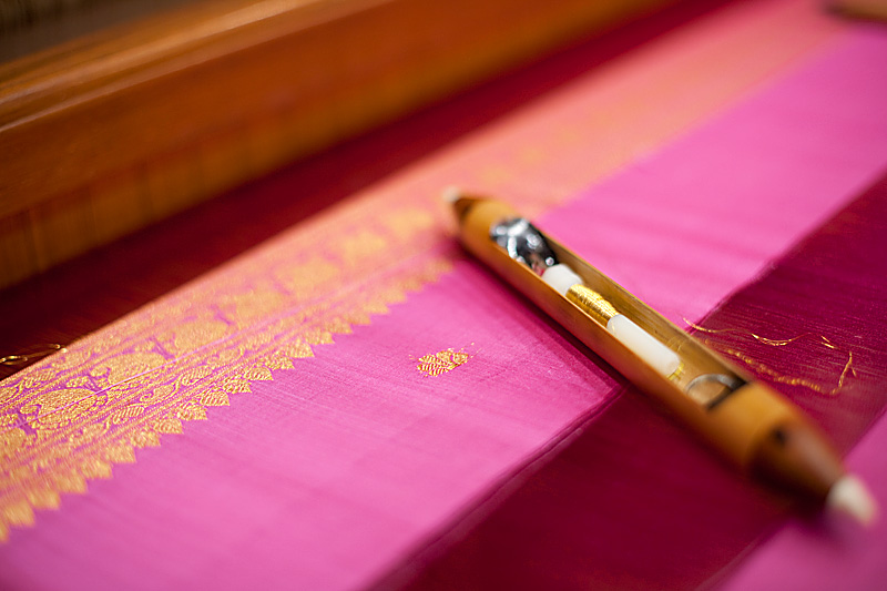 A shuttle rests on an unfinished silk saree. - Tirunelveli, Tamil Nadu, India - Daily Travel Photos