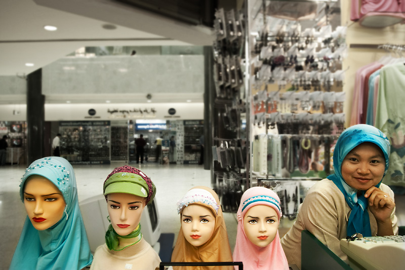 A Muslim woman stands in line with scarfed mannequins. - Bandar Seri Begawan, Brunei - Daily Travel Photos