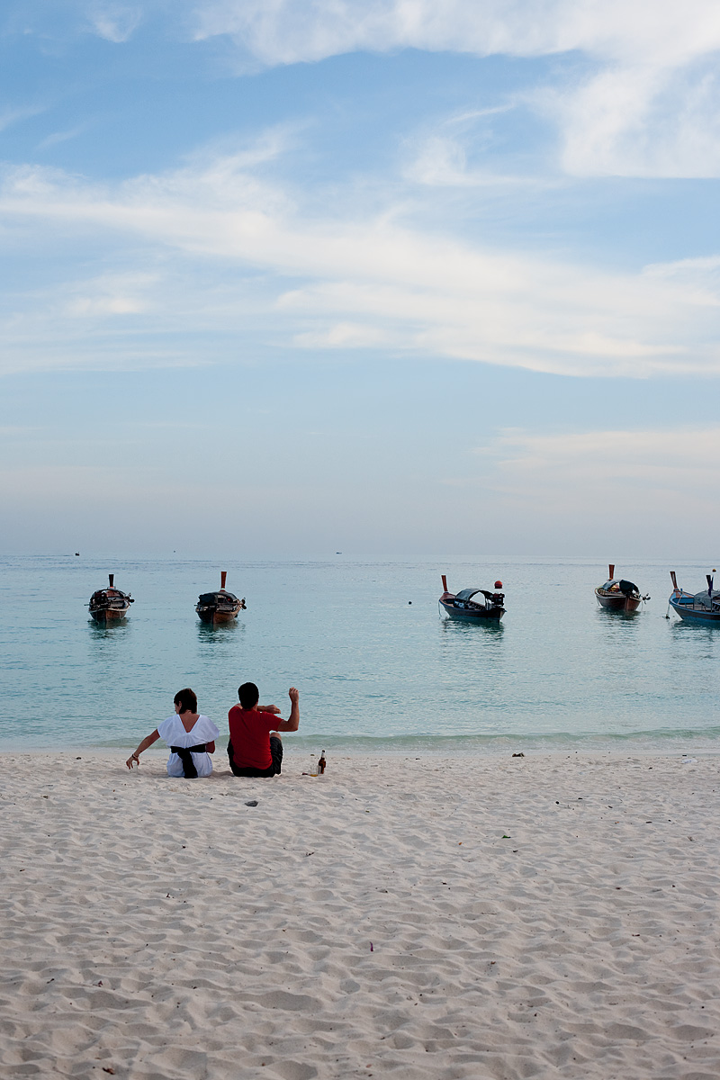 A bored Spanish man throws a rock into a calm ocean. - Ko Lipe, Thailand - Daily Travel Photos