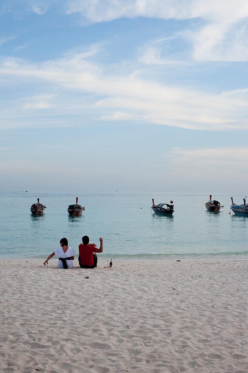 A bored Spanish man throws a rock into a calm ocean. - Ko Lipe, Thailand - Daily Travel Photos
