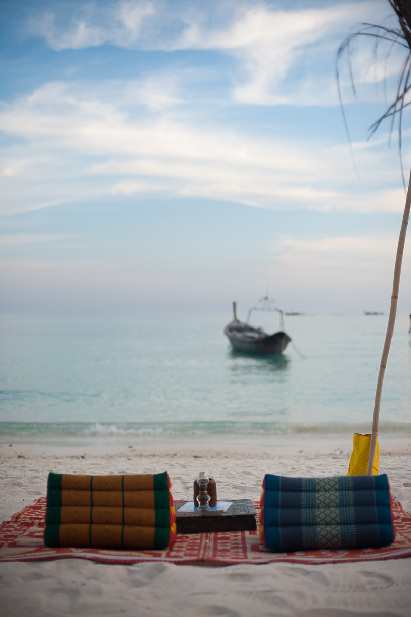 A mat on the sand with a table and cushions, part of a beach bar, look directly onto the ocean. - Ko Lipe, Thailand - Daily Travel Photos