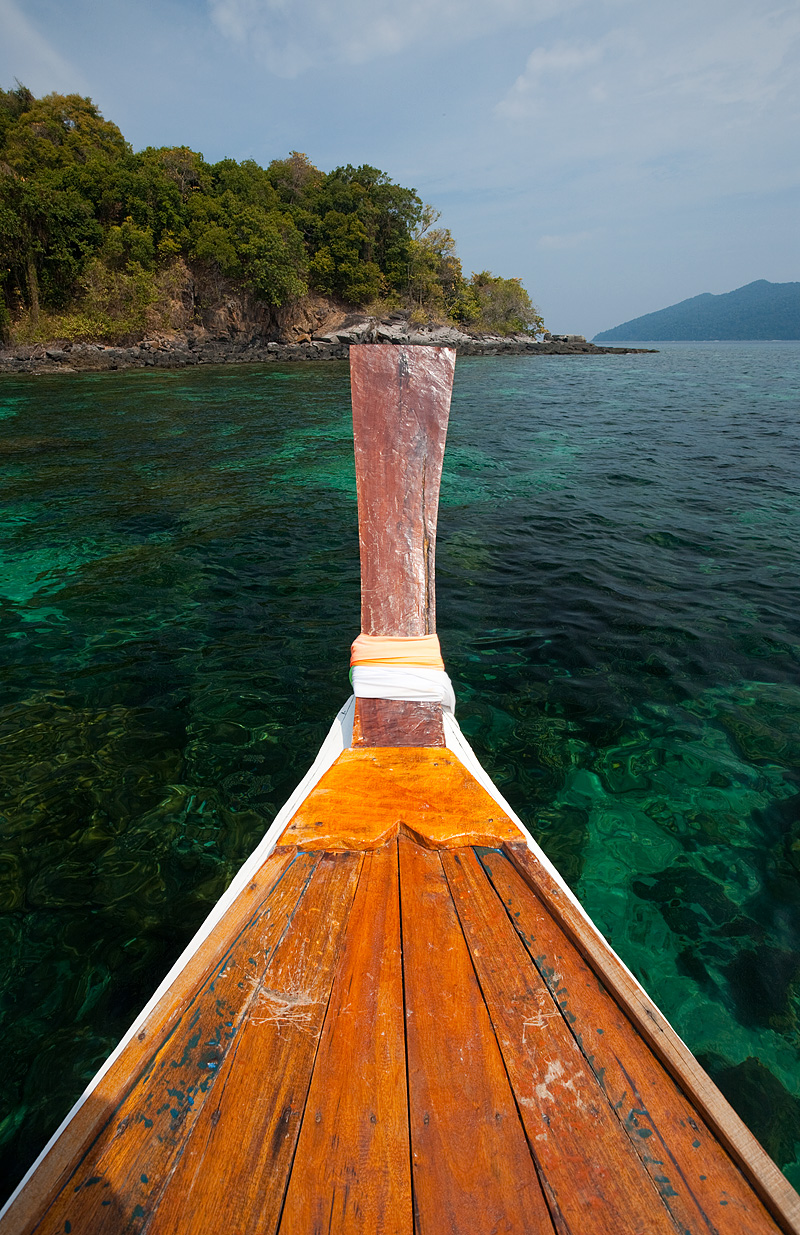 The bow of a longtail boat overlooking crystal clear snorkeling water. - Ko Lipe, Thailand - Daily Travel Photos