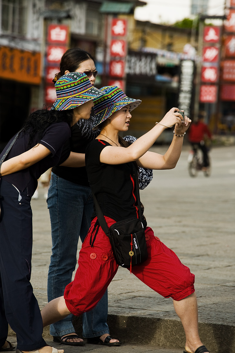 A Chinese woman strikes an atypical picture snapping position. - Dali, Yunnan, China - Daily Travel Photos