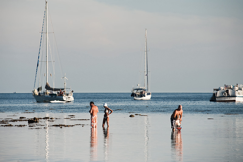 Tourists search the low-tide waters for sea life and souvenir shells. - Ko Lipe, Thailand - Daily Travel Photos