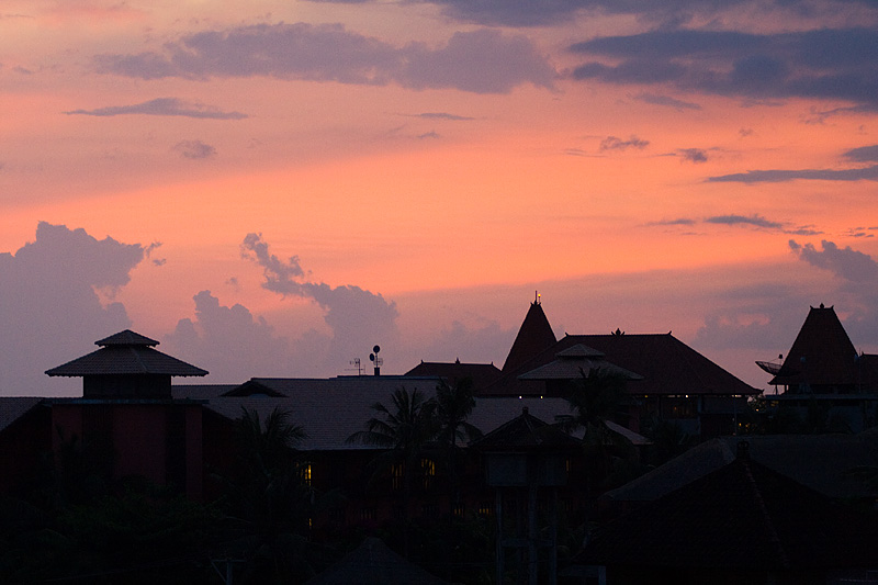 The sky lights up purple and pink above the rooftops of a hotel. - Kuta, Bali, Indonesia - Daily Travel Photos