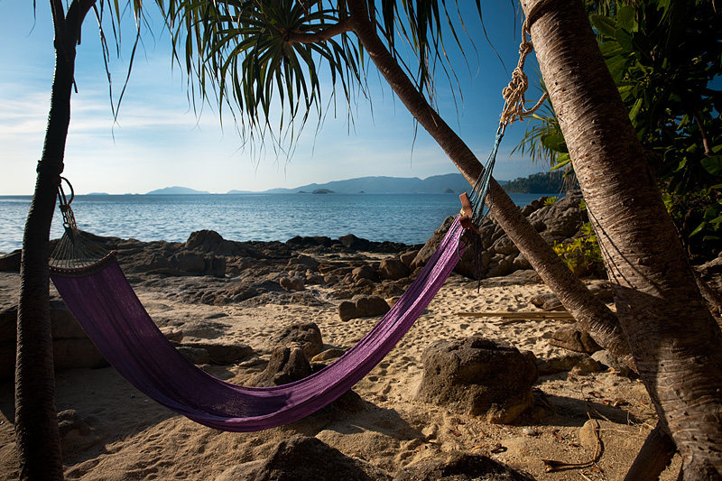 An unused hammock swings on a rocky beach. - Ko Lipe, Thailand - Daily Travel Photos