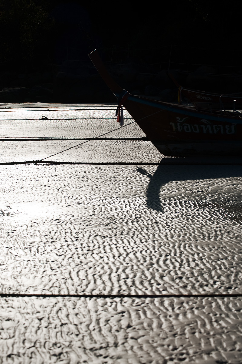 A grounded longtail boat is seen tied to patterned ropes on a richly textured sea floor. - Ko Lipe, Thailand - Daily Travel Photos