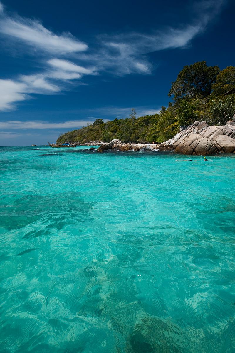 A snorkeler maneuvers around a small set of rocky outcroppings. - Ko Lipe, Thailand - Daily Travel Photos