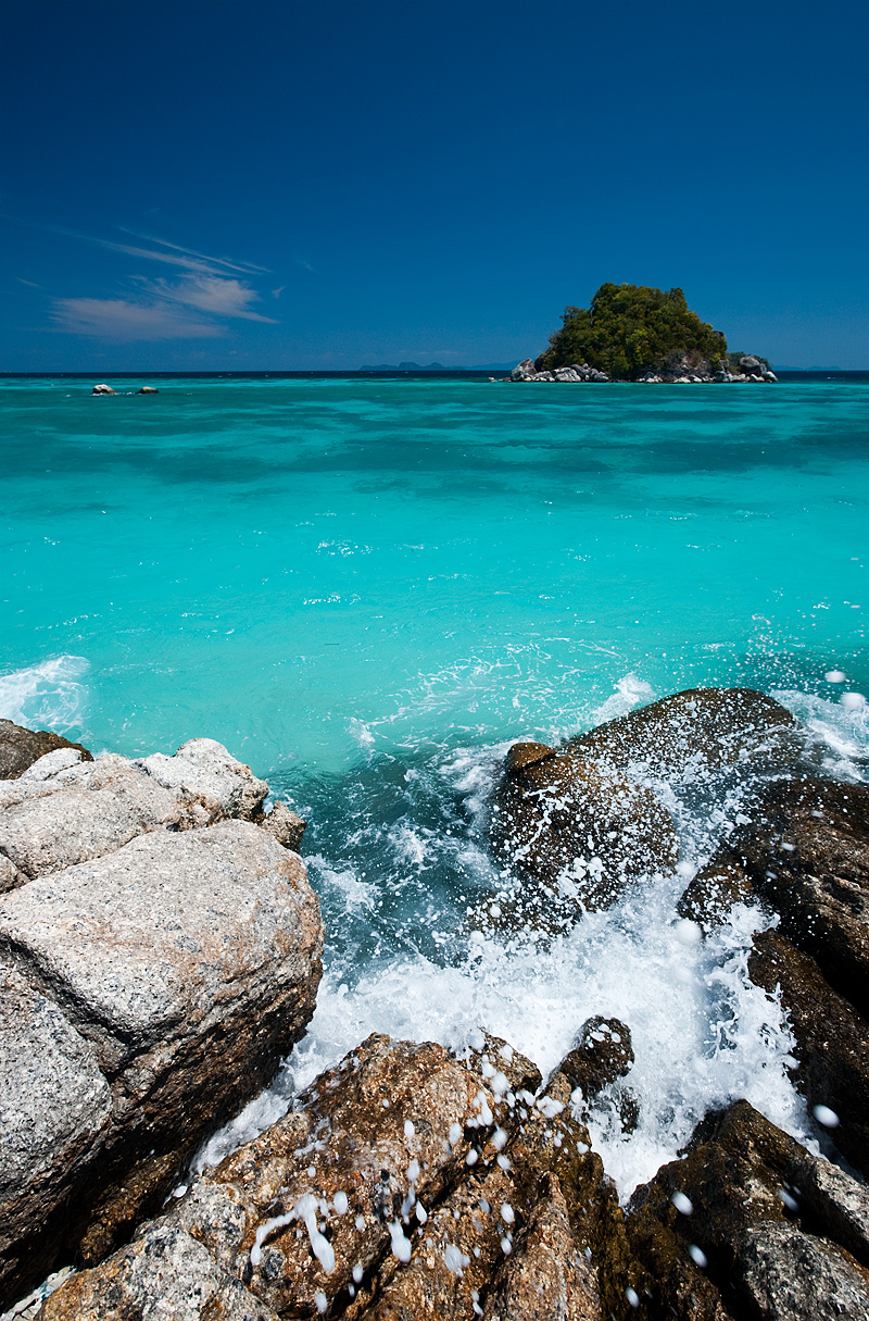 A small wave breaks on rocks on shore on Sunrise Beach. - Ko Lipe, Thailand - Daily Travel Photos