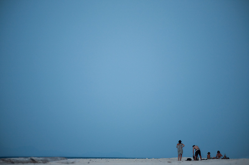 A wide telephoto view of a vacationing family packing after the sunset.  - Ko Lipe, Thailand - Daily Travel Photos