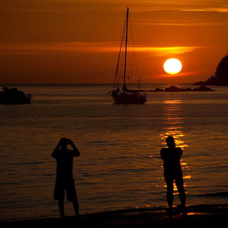 A pair of tourists capture a photo of the setting sun. - Ko Lipe, Thailand - Daily Travel Photos
