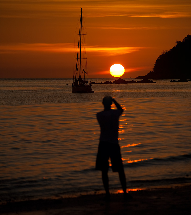 A tourist captures a photo of the setting sun. - Ko Lipe, Thailand - Daily Travel Photos