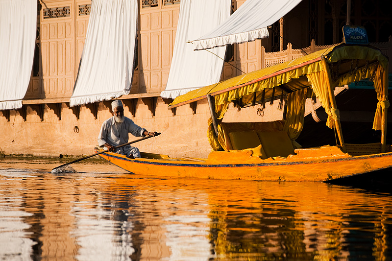 A bearded Kashmiri man paddles past a boathouse on Dal Lake. - Srinagar, Kashmir, India - Daily Travel Photos