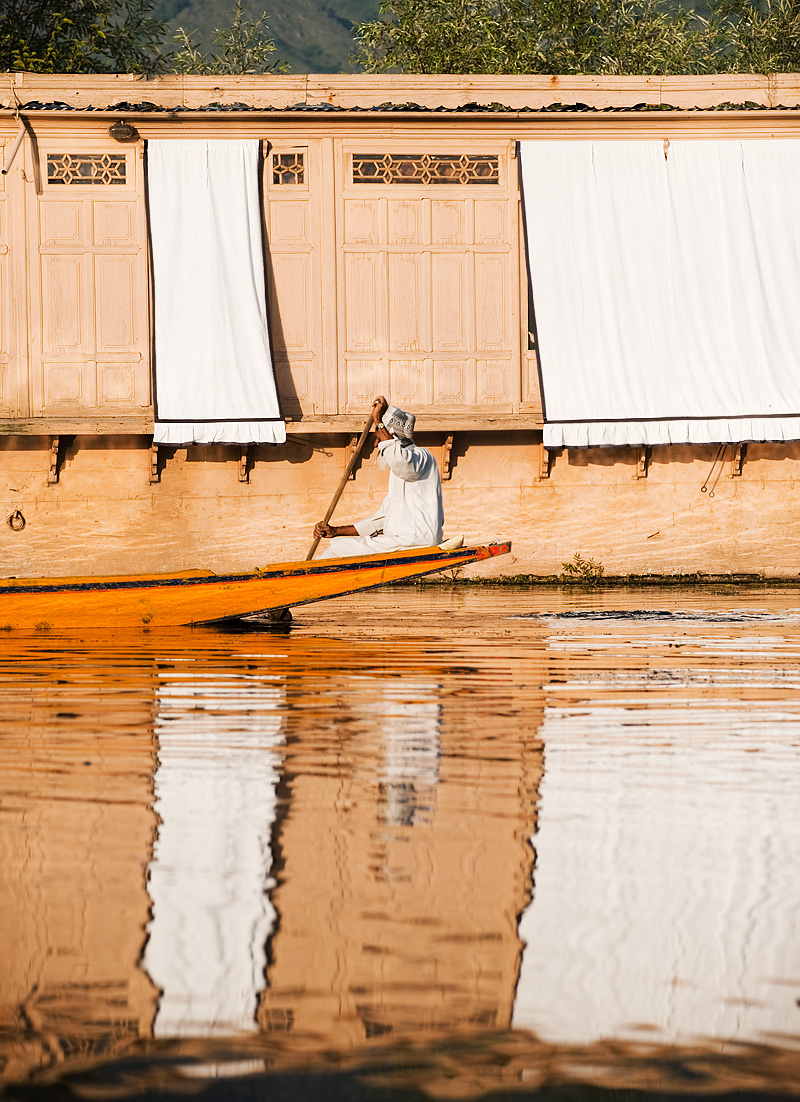 A Kashmiri man boats past the shaded windows of a boathouse on Dal Lake. - Srinagar, Kashmir, India - Daily Travel Photos