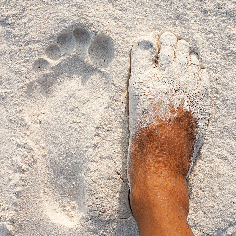 A footprint and a sand-caked foot on Pattaya beach. - Ko Lipe, Thailand - Daily Travel Photos