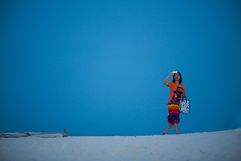 A Thai woman walks sideways while hastily snapping a camera-phone photo. - Ko Lipe, Thailand - Daily Travel Photos