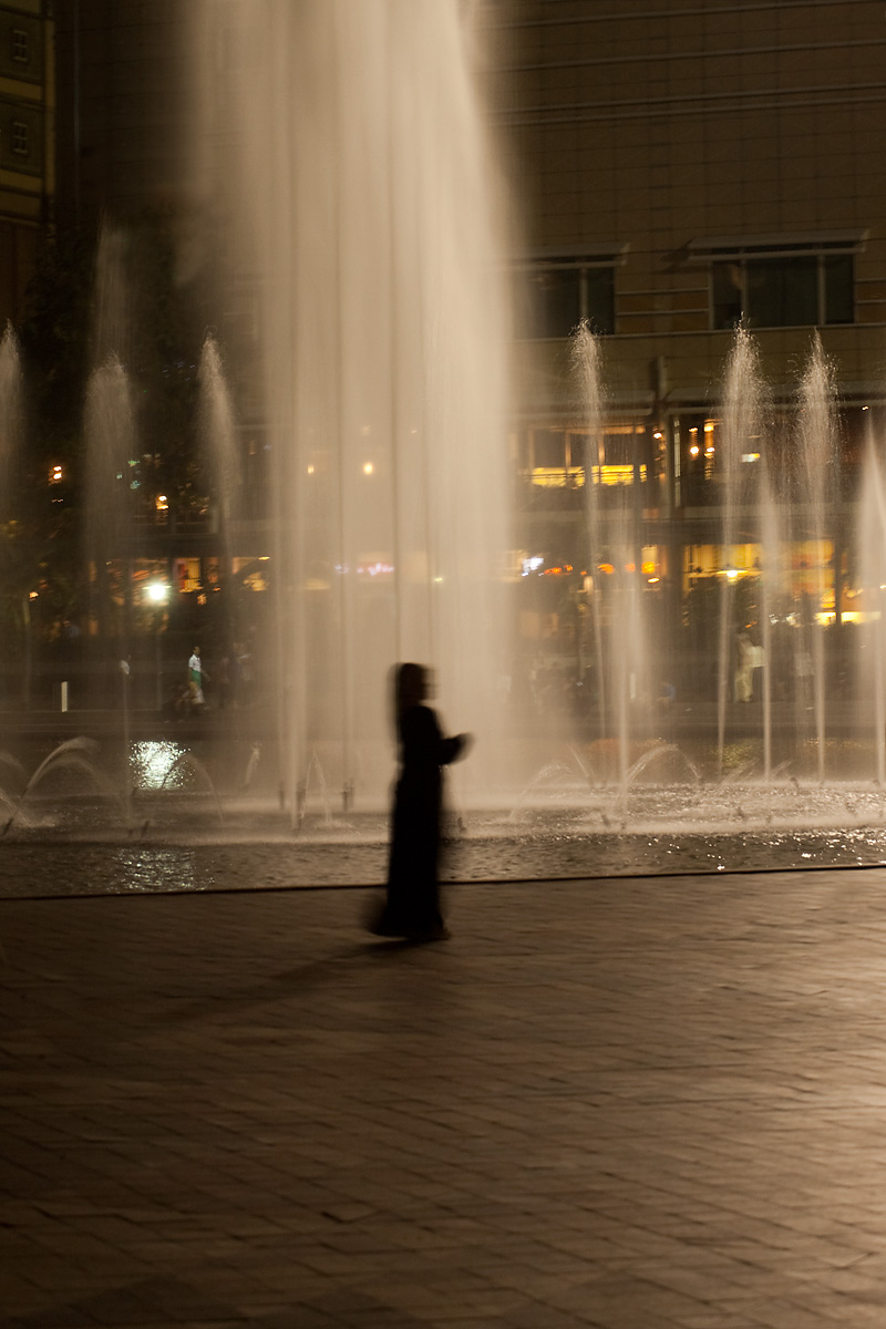A female Arab tourist walks in front of a backlit water fountain. - Kuala Lumpur, Malaysia - Daily Travel Photos