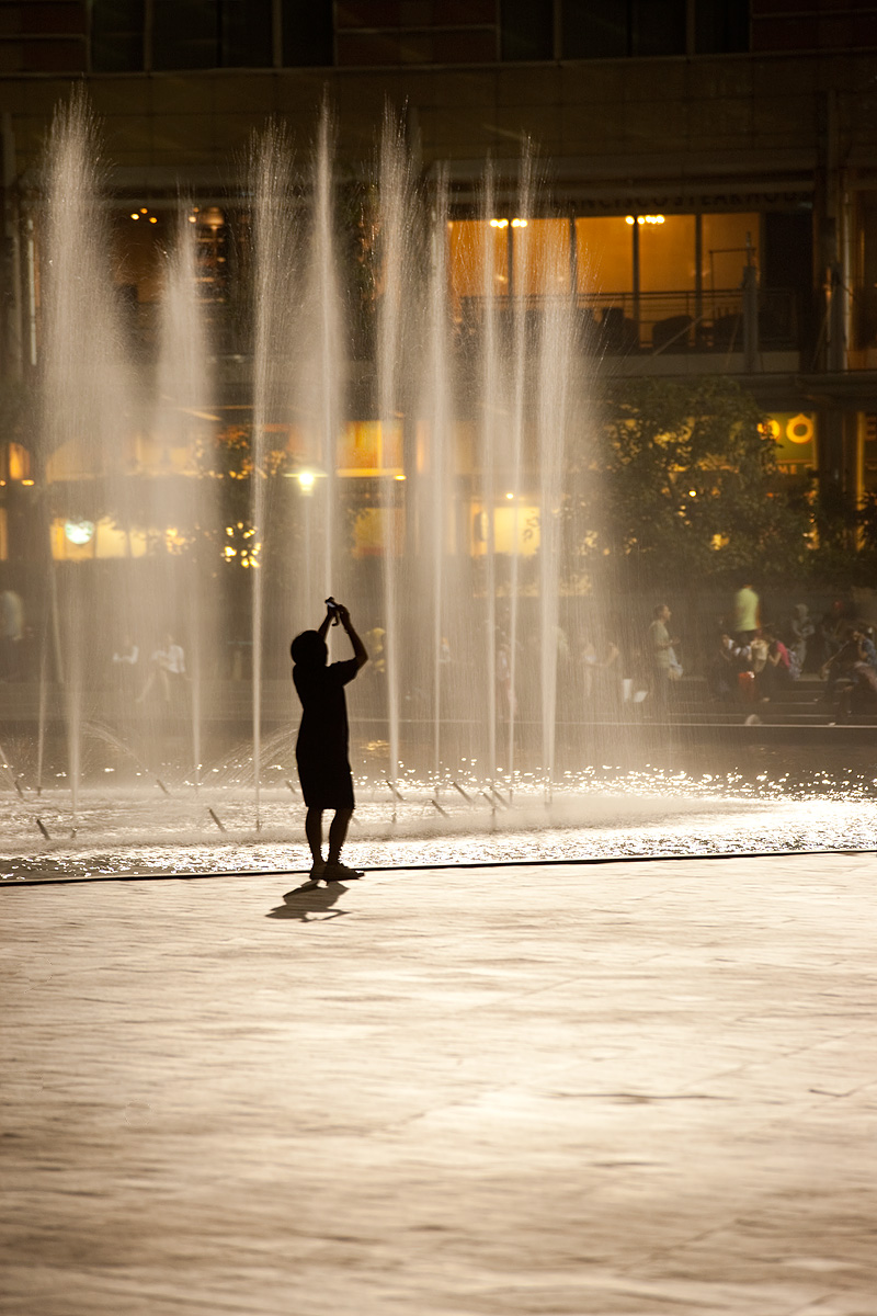 A young Chinese boy stands in front of a backlit fountain pointing his camera at the Petronas Twin Towers.  - Kuala Lumpur, Malaysia - Daily Travel Photos