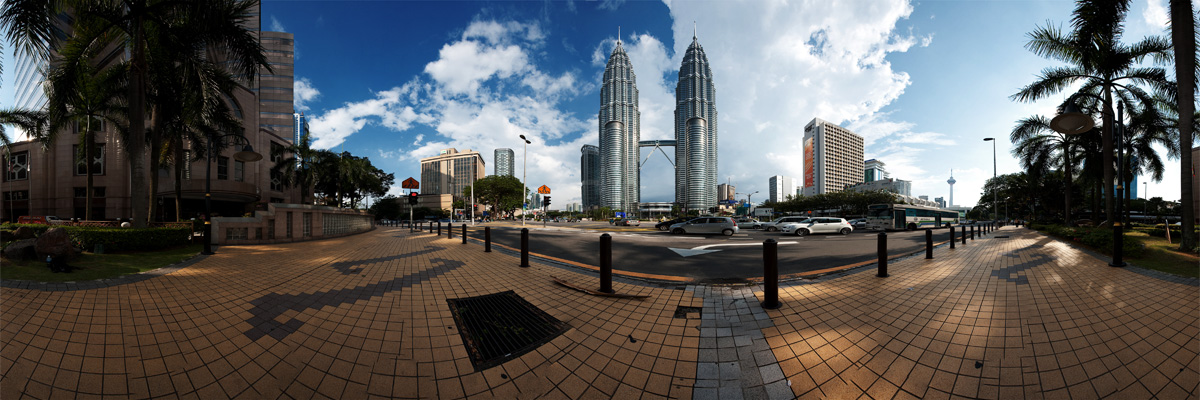 A panorama of the Petronas Twin Towers seen from the sidewalk across the street. - Kuala Lumpur, Malaysia - Daily Travel Photos