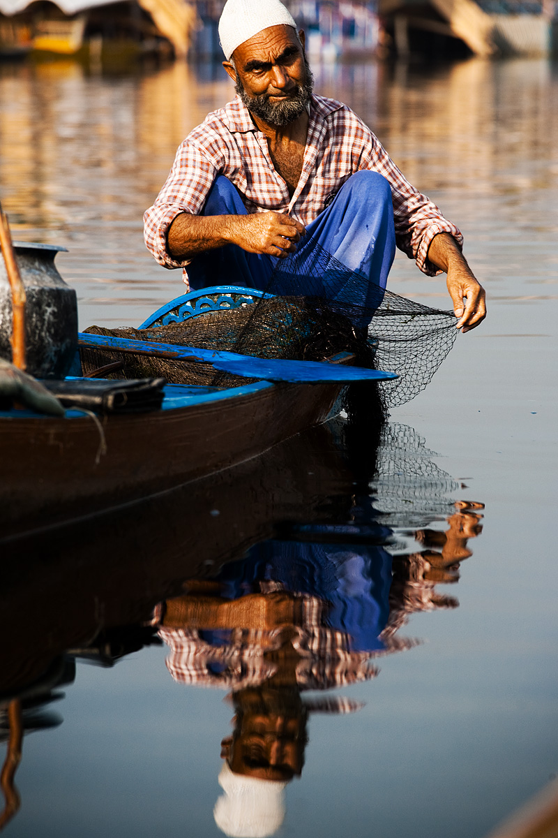 A fisherman on Dal Lake tends to his net. - Srinagar, Kashmir, India - Daily Travel Photos