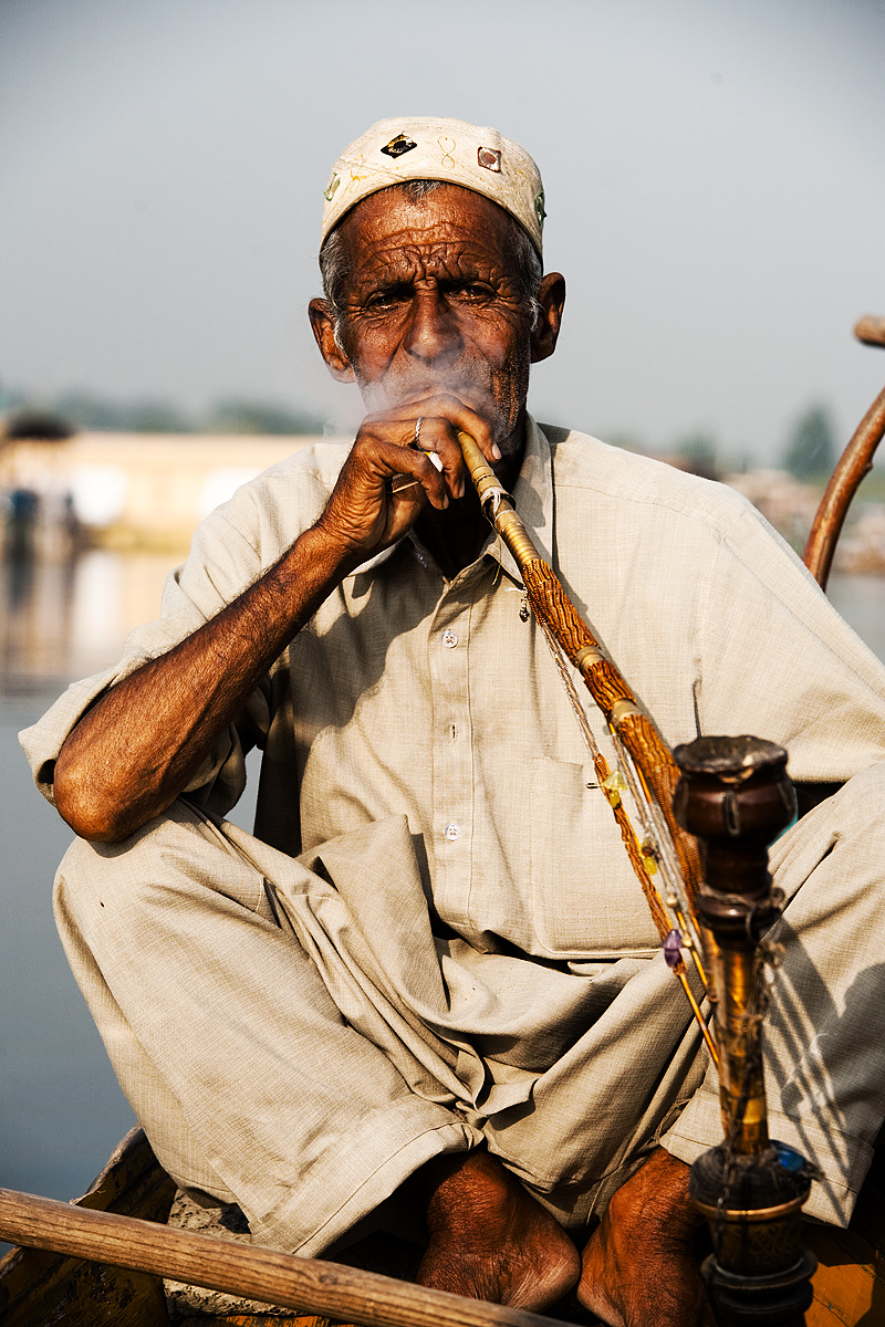 A shikara driver smokes a sheesha pipe while resting from paddling tourists around Dal Lake. - Srinagar, Kashmir, India - Daily Travel Photos