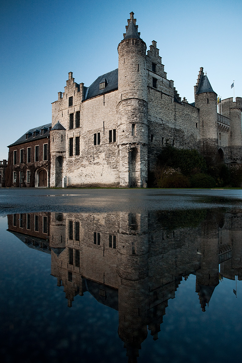 Former King's castle, Het Steen (The Stone), reflected in a puddle of water. - Antwerp, Belgium - Daily Travel Photos