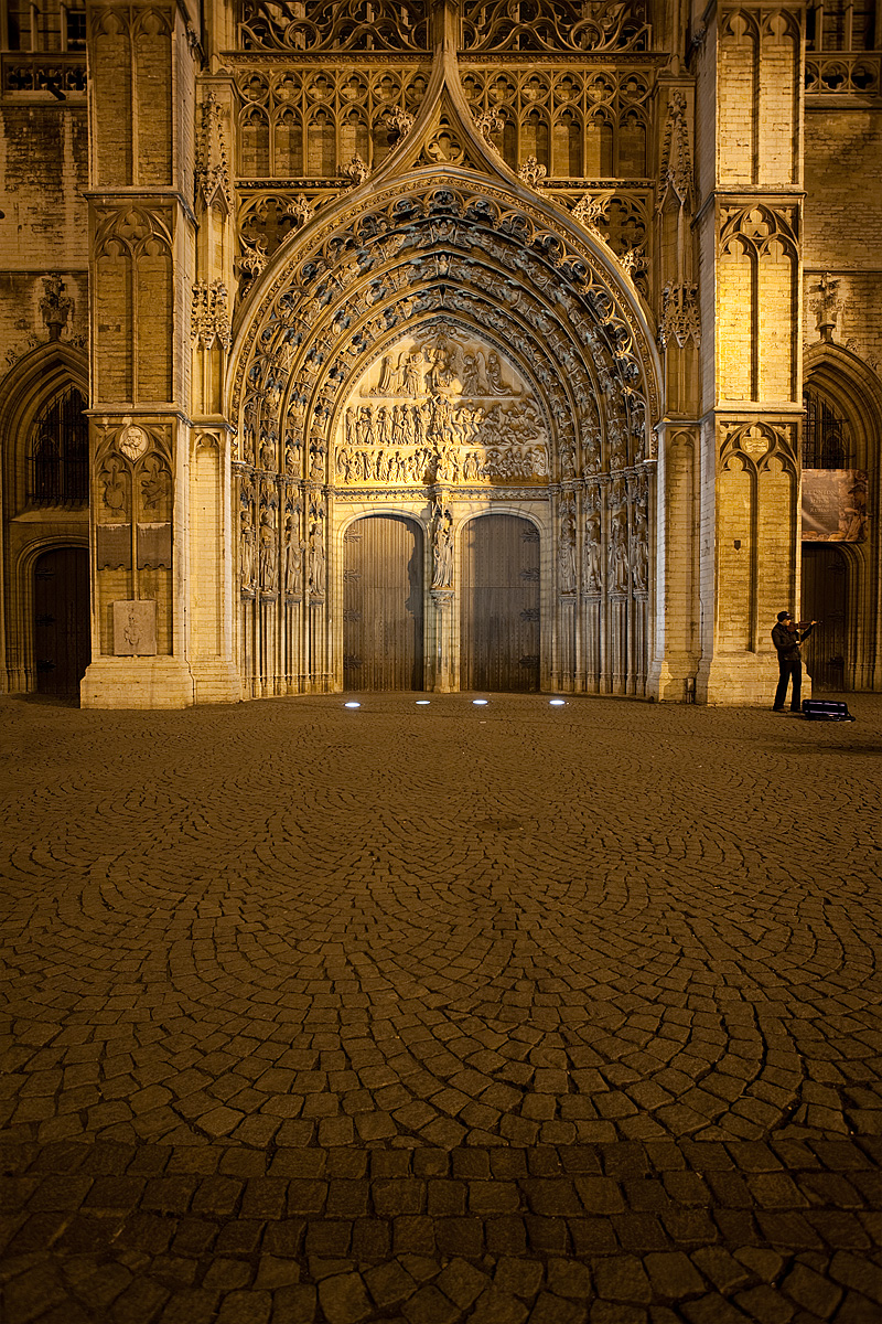 A street violinist performs outside the entrance of the Cathedral of Our Lady. - Antwerp, Belgium - Daily Travel Photos
